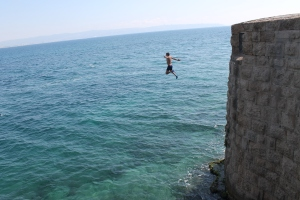 Boy leaping from Ottoman old town ramparts in Akko
